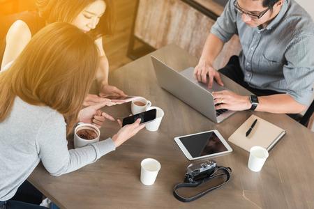 スマート フォン タブレットとラップトップは、概念的なもののインターネットを使用している間の互いにコーヒー ショップのチャットで会う友人