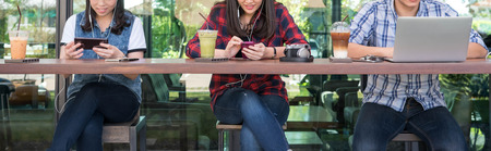 three people using smartphone, tablet, and laptop in coffee shop, internet of things conceptual