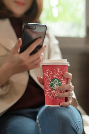 Bangkok ,Thailand December 12 : woman hold starbucks hot beverage cup in Christmas theme using smartphone, Iphone7