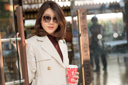 trademark: Bangkok ,Thailand December 12 : woman wearing coat and sun glasses  hold Starbucks hot beverage cup in Christmas theme step out from Starbucks cafe Editorial