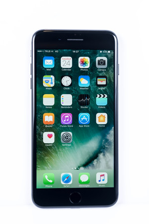 BANGKOK, THAILAND - NOVEMBER 20, 2016: Iphone7 Plus jet black series front view with default home scren on white plain floor, new generation of smartphone, smartphone without headphone jack