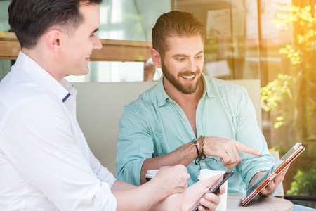 Two Westerner Business men talk and use smart phone Stock Photo