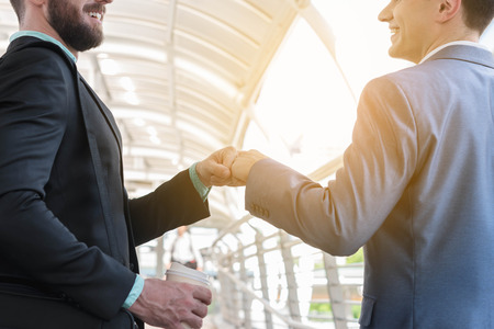 make public: Two Westerner Business men talk and make fist bump on the public area of the walk way Stock Photo