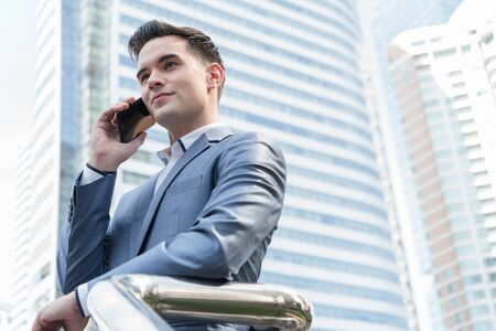 Westerner Business man talking via smart phone with skyscraper in background Stock Photo