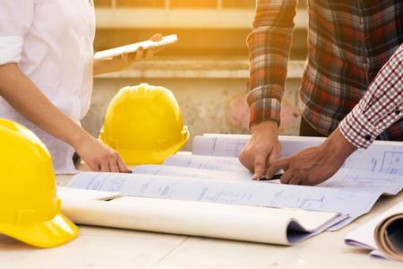 건설 현장에서 야외 작업 테이블에 청사진을 세 건설 노동자 스톡 콘텐츠