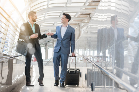 make public: Two Westerner Business men talk and use smart phone make fist bump on the public area of the walk way Stock Photo