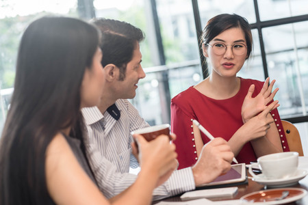 3 people meeting in coffee shop, business casual conceptual