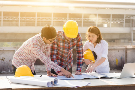 three construction engineers working outdoors in construction site Stock Photo