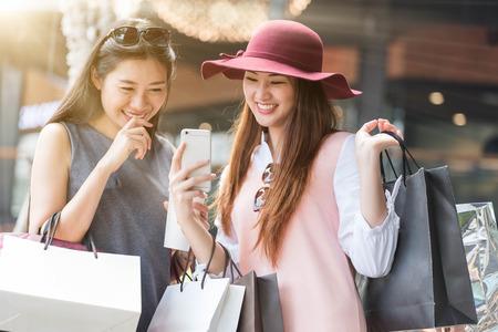 2 つの女性を一緒にショッピング バッグを手にして、スマート フォン、ショッピング オンライン ショッピング概念
