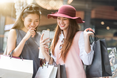 happy shopping: two woman shopping together with shopping bags in hand and using smartphone, shopping online conceptual