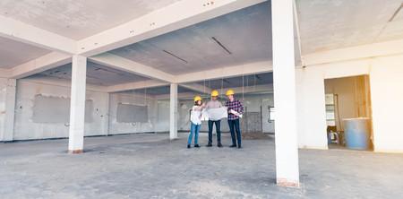 tres ingenieros de la construcción que trabajan juntos en la planificación del edificio lateral para la renovación Foto de archivo