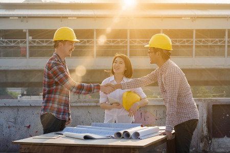 three construction engineers finished working shaking hands outdoors in construction site with blueprint on table