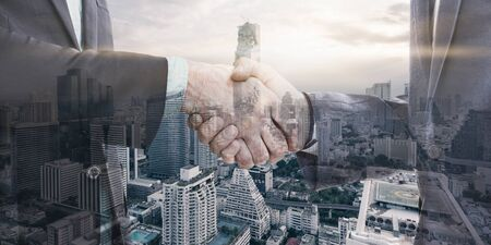 international business agreement: Double exposure of two businessman shaking hands with city in background
