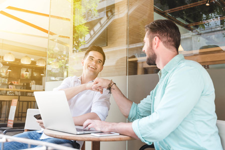 Two Westerner Business men talk and use smart phone and laptop make fist bump Stock Photo