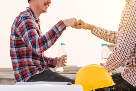 three construction engineers finished working make fist bump at outdoors in construction site with blueprint on table