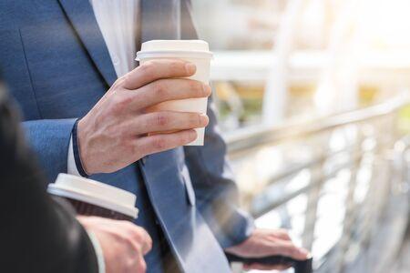 Zwei westliche Geschäftsleute sprechen mit Pappbecher heißen Kaffee in den Händen