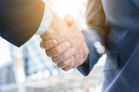 Hand shake of two businessman with sun flare, business conceptual Stok Fotoğraf - 70792920