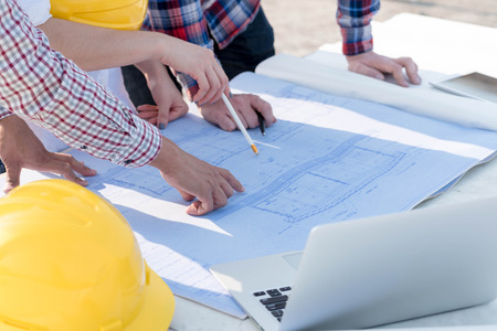 three construction engineers working outdoors in construction site with blueprint on table