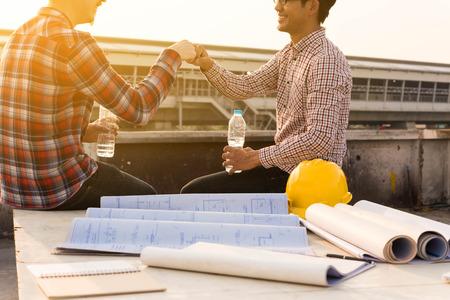 drei Bauingenieure fertig arbeiten machen Faust Bump im Freien auf Baustelle mit Blaupause auf dem Tisch