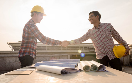 Three construction engineers working outdoors in construction three construction engineers finished working shaking hands outdoors in construction site with blueprint on table photo malvernweather Images