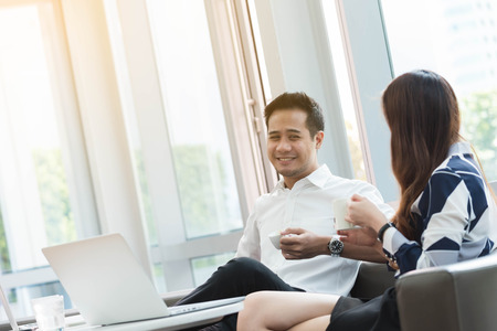 Two asian coworkers use laptop work together having coffee in afternoon, man with crafty eye Stock Photo