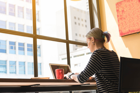 Due lavoratori freelance che lavorano in caffè, lavoratore concettuale di Nomad, coppia lavorano insieme in caffè con il computer portatile Archivio Fotografico - 82904950