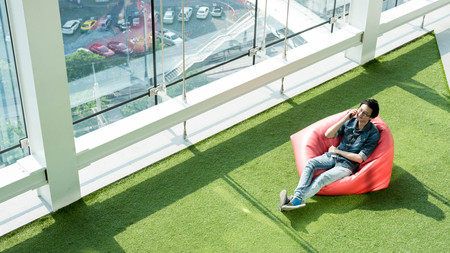 Man talk via smartphone on bean bag in afternoon, freelance conceptual lifestyle, internet in everyday life Stock Photo