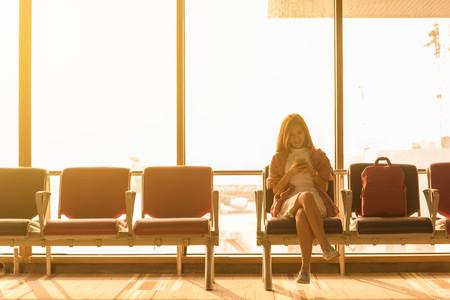 世界探検の概念のフライトのため空港待機で耳電話で旅行バッグ使用スマート フォンで空港で座っている若い美しい女性