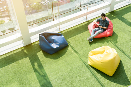 Man use smartphone on bean bag in afternoon, freelance conceptual lifestyle, internet in everyday life