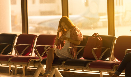 Young beautiful woman sit in airport with travel bag use smartphone with ear phone at airport wait for flight, world exploration concept