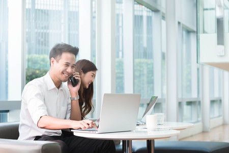 Two asian coworkers use laptop work together