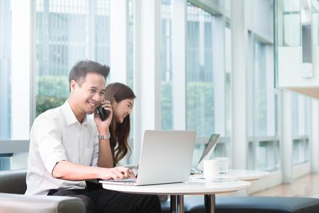 2 つのアジアの同僚が一緒に作業をノート パソコンを使用します。 写真素材