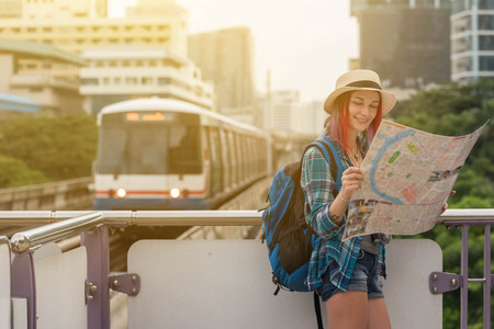 Woman westerner looking at map during city tour in the morning, planning for todays trip Stock Photo