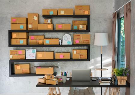 Bureau met laptop bij het raam met pakketdoos voorbereid voor bezorging