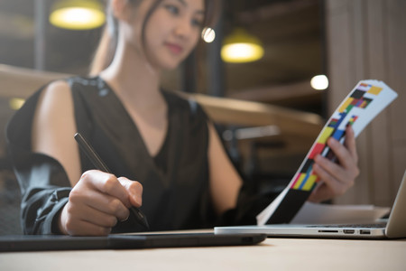 Beautiful asian woman designer in black dress working with mouse pen while look at color chart Stock Photo