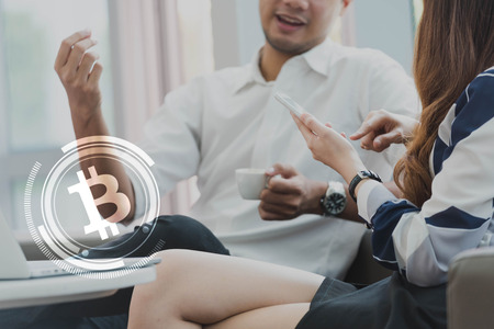 Two asian earning money from bitcoin use smartphone and laptop Zdjęcie Seryjne
