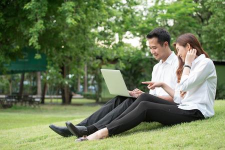 사업가 및 여자 사용 노트북 공원에서 함께 잔디에 앉아