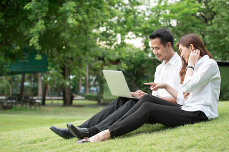 Businessman and woman use laptop in park, sit on grass together Archivio Fotografico