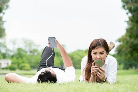 남자와 여자는 흰 셔츠에 거짓말 공공 공원에서 잔디에 누워 스마트 폰 및 귀 전화 함께 기술 개념