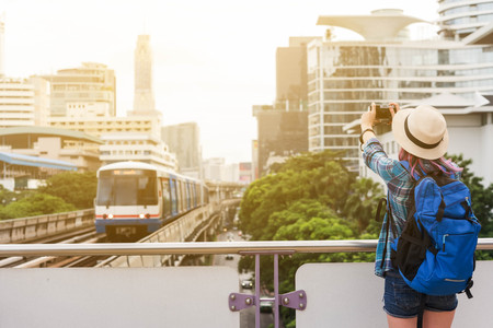 Woman westerner taking photo of sky train in city in the morning