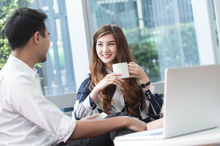 Two asian coworkers use laptop and smartphone work together having coffee in afternoon