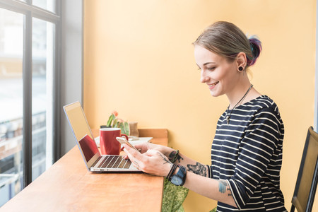 Russian woman working as freelance use smartphone and laptop in coffee shop