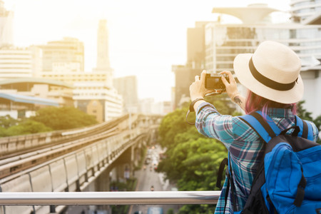 Woman westerner taking photo of sky train track in city in the morning