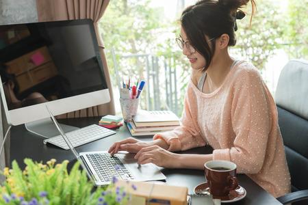 自宅で働く若い美しい女の子、若い起業家の概念 写真素材