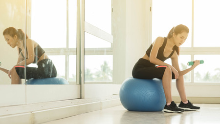 Young beautiful woman lift dumbbell sit on ball