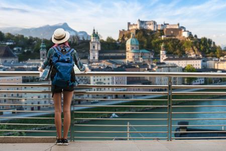 Westliche Reise der Frau im Rucksack mit der Karte, die Stadtansicht der Schloss-Salzburg-Stadt in Österreich betrachtet