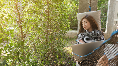 Young woman sleeping in hammock while use laptop, freelance life style conceptual, work anywhere