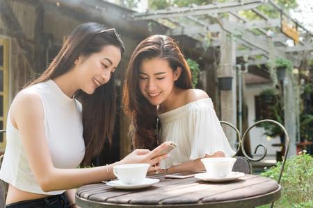 Dos hermosas mujeres independientes usan las redes sociales en el teléfono inteligente en la cafetería, el estilo de vida de la generación moderna