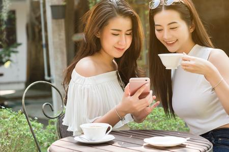Schönes Gebrauchssocial media der freiberuflichen Frau zwei auf Smartphone in der Kaffeestube, Lebensstil der modernen Generation
