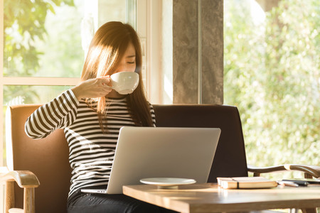 Beautiful young teenage woman freelance work with laptop have coffee at coffee shop in with sun light, freelance lifestyle conceptual, life of coffee lover